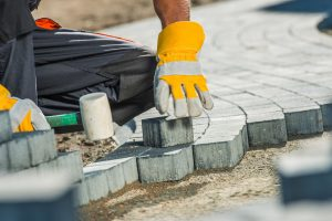 62415729 - brock paving closeup photo. construction worker paving brick pathway.